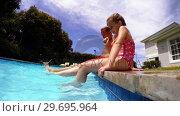 Купить «Parent and daughter sitting on poolside and shaking their legs in pool water», видеоролик № 29695964, снято 29 ноября 2016 г. (c) Wavebreak Media / Фотобанк Лори