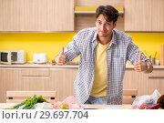 Купить «Young man calculating expences for vegetables in kitchen», фото № 29697704, снято 3 августа 2018 г. (c) Elnur / Фотобанк Лори