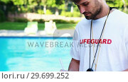 Купить «Smiling lifeguard writing on clipboard at poolside», видеоролик № 29699252, снято 29 ноября 2016 г. (c) Wavebreak Media / Фотобанк Лори