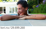 Купить «Woman smiling while leaning over the swimming pool», видеоролик № 29699260, снято 29 ноября 2016 г. (c) Wavebreak Media / Фотобанк Лори
