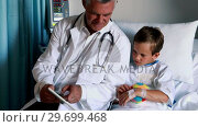 Купить «Male doctor using digital tablet during visit in ward», видеоролик № 29699468, снято 5 ноября 2016 г. (c) Wavebreak Media / Фотобанк Лори