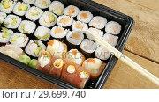 Купить «Sushi rolls with salmon in plastic tray», видеоролик № 29699740, снято 8 декабря 2016 г. (c) Wavebreak Media / Фотобанк Лори