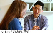 Купить «Business executives discussing over document», видеоролик № 29699908, снято 23 октября 2016 г. (c) Wavebreak Media / Фотобанк Лори