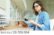 Купить «Female executive looking at glass sheet while using digital tablet», видеоролик № 29700004, снято 23 октября 2016 г. (c) Wavebreak Media / Фотобанк Лори