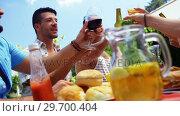 Купить «Group of happy friends toasting beer bottles and glasses at outdoors barbecue party», видеоролик № 29700404, снято 1 февраля 2017 г. (c) Wavebreak Media / Фотобанк Лори