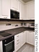 Купить «Beige kitchen with oven and a microwave», фото № 29700516, снято 29 октября 2018 г. (c) Володина Ольга / Фотобанк Лори