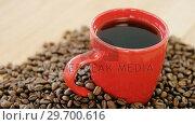 Купить «Black coffee surrounded with roasted beans», видеоролик № 29700616, снято 6 октября 2016 г. (c) Wavebreak Media / Фотобанк Лори