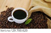 Купить «Coffee cup with coffee beans and leaf», видеоролик № 29700620, снято 6 октября 2016 г. (c) Wavebreak Media / Фотобанк Лори