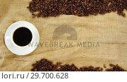 Купить «Coffee cup with coffee beans arranged on sack», видеоролик № 29700628, снято 6 октября 2016 г. (c) Wavebreak Media / Фотобанк Лори