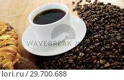 Купить «Coffee with roasted coffee beans and croissant», видеоролик № 29700688, снято 6 октября 2016 г. (c) Wavebreak Media / Фотобанк Лори