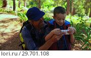 Купить «Father helping son using mobile phone in the park», видеоролик № 29701108, снято 2 марта 2017 г. (c) Wavebreak Media / Фотобанк Лори