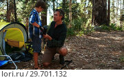 Купить «Father teaching son to use trekking pole outside tent», видеоролик № 29701132, снято 2 марта 2017 г. (c) Wavebreak Media / Фотобанк Лори