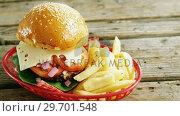 Купить «Hamburger and french fries in basket», видеоролик № 29701548, снято 13 января 2017 г. (c) Wavebreak Media / Фотобанк Лори