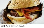 Купить «Hamburger wrapped in a foil on table», видеоролик № 29701672, снято 13 января 2017 г. (c) Wavebreak Media / Фотобанк Лори