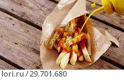 Купить «Mustard sauce being squeezed over french fried chips on tray», видеоролик № 29701680, снято 13 января 2017 г. (c) Wavebreak Media / Фотобанк Лори