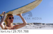 Купить «Young woman carrying surfboard on head at beach», видеоролик № 29701788, снято 1 марта 2017 г. (c) Wavebreak Media / Фотобанк Лори
