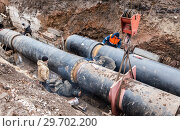 Купить «Repair work of heating duct. The workers, welders made by electric welding on large iron pipes at a depth of excavated trench», фото № 29702200, снято 1 октября 2017 г. (c) FotograFF / Фотобанк Лори