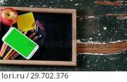 Купить «Apple and mobile phone with school supplies on slate», видеоролик № 29702376, снято 5 апреля 2017 г. (c) Wavebreak Media / Фотобанк Лори