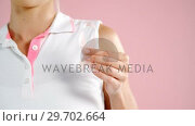 Mid-section of woman holding breast cancer awareness ribbon. Стоковое видео, агентство Wavebreak Media / Фотобанк Лори
