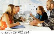 Купить «Team of executives interacting with each other while working in the office», видеоролик № 29702824, снято 26 марта 2017 г. (c) Wavebreak Media / Фотобанк Лори