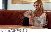 Купить «Woman sitting on sofa in restaurant 4k», видеоролик № 29703516, снято 28 марта 2017 г. (c) Wavebreak Media / Фотобанк Лори