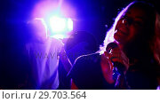 Купить «Female singer singing into a microphone 4k», видеоролик № 29703564, снято 7 марта 2017 г. (c) Wavebreak Media / Фотобанк Лори