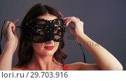 Купить «Beautiful woman wearing masquerade mask 4k», видеоролик № 29703916, снято 22 мая 2017 г. (c) Wavebreak Media / Фотобанк Лори