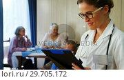 Купить «Portrait of female doctor reading reports 4k», видеоролик № 29705172, снято 28 апреля 2017 г. (c) Wavebreak Media / Фотобанк Лори