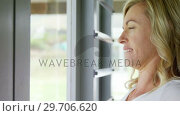 Купить «Woman stretching her arms near the window 4k», видеоролик № 29706620, снято 24 марта 2017 г. (c) Wavebreak Media / Фотобанк Лори