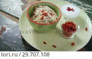Купить «Plate of breakfast cereal with raisin and yogurt on wooden table 4k», видеоролик № 29707108, снято 13 июня 2017 г. (c) Wavebreak Media / Фотобанк Лори