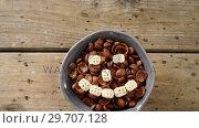 Купить «Chocolate cornflakes with honeycomb cereal forming smiley face in bowl 4k», видеоролик № 29707128, снято 13 июня 2017 г. (c) Wavebreak Media / Фотобанк Лори