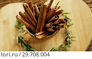 Купить «Cinnamon sticks and rosemary arranged on wooden board 4k», видеоролик № 29708004, снято 5 июня 2017 г. (c) Wavebreak Media / Фотобанк Лори