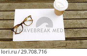 Купить «Blank paper with coffee and spectacles on wooden table 4k», видеоролик № 29708716, снято 16 мая 2017 г. (c) Wavebreak Media / Фотобанк Лори