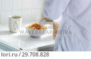 Купить «Man pouring breakfast cereal into bowl in kitchen 4k», видеоролик № 29708828, снято 13 октября 2017 г. (c) Wavebreak Media / Фотобанк Лори