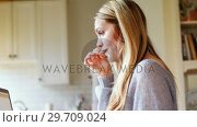 Купить «Woman using laptop while having breakfast 4k», видеоролик № 29709024, снято 5 апреля 2017 г. (c) Wavebreak Media / Фотобанк Лори