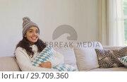 Купить «Happy woman in warm clothing sitting on sofa watching television 4K 4k», видеоролик № 29709360, снято 31 мая 2017 г. (c) Wavebreak Media / Фотобанк Лори