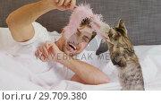 Купить «Smiling young man lying on bed playing with his tabby cat 4K 4k», видеоролик № 29709380, снято 31 мая 2017 г. (c) Wavebreak Media / Фотобанк Лори