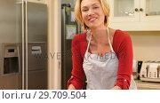 Купить «Smiling woman wearing apron spreading dough in baking tin 4K 4k», видеоролик № 29709504, снято 10 августа 2017 г. (c) Wavebreak Media / Фотобанк Лори