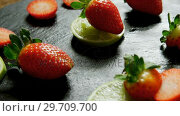 Купить «Sliced strawberries and lemon on round tray 4K 4k», видеоролик № 29709700, снято 12 июня 2017 г. (c) Wavebreak Media / Фотобанк Лори