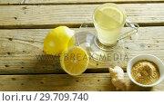 Купить «Lemon tea with ginger powder on wooden table 4k», видеоролик № 29709740, снято 12 июня 2017 г. (c) Wavebreak Media / Фотобанк Лори