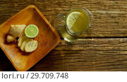 Купить «Lemon tea with ginger and lemon on wooden table 4k», видеоролик № 29709748, снято 12 июня 2017 г. (c) Wavebreak Media / Фотобанк Лори