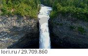 Купить «Beautiful water fall through forest cliff on a sunny day 4k», видеоролик № 29709860, снято 3 августа 2017 г. (c) Wavebreak Media / Фотобанк Лори
