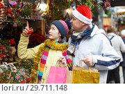 Купить «Girl with father choosing Xmas decoration», фото № 29711148, снято 8 декабря 2018 г. (c) Яков Филимонов / Фотобанк Лори