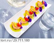 Купить «Tasty seafood ceviche from salmon with figs, kiwi and cumquat at plate», фото № 29711180, снято 21 октября 2019 г. (c) Яков Филимонов / Фотобанк Лори