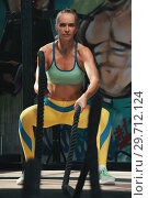 Купить «Portrait of sporty woman training with battle ropes», фото № 29712124, снято 6 сентября 2018 г. (c) Pavel Biryukov / Фотобанк Лори