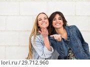 Купить «Two young women blowing a kiss on urban wall.», фото № 29712960, снято 7 марта 2018 г. (c) Ingram Publishing / Фотобанк Лори