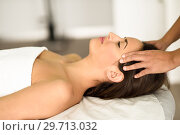 Купить «Young smiling woman receiving a head massage in a spa center.», фото № 29713032, снято 23 ноября 2017 г. (c) Ingram Publishing / Фотобанк Лори
