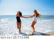 Купить «Two women in swimsuit having fun on the beach», фото № 29713048, снято 24 сентября 2017 г. (c) Ingram Publishing / Фотобанк Лори