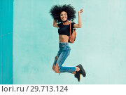 Купить «Young mixed woman with afro hair jumping outdoors.», фото № 29713124, снято 23 мая 2018 г. (c) Ingram Publishing / Фотобанк Лори