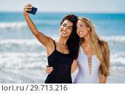 Купить «Two women taking selfie photograph with smartphone in the beach», фото № 29713216, снято 24 сентября 2017 г. (c) Ingram Publishing / Фотобанк Лори